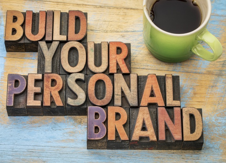 """"""" blocks spelling out build your personal brand next to a cup of coffee"""""""